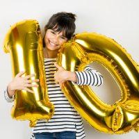 Ein Mädchen posiert mit Luftballons