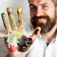 Mann mit Farbe an der Hand